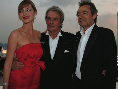 TV presenter Louise Bourgeois with actor Alain Delon and TV presenter Michel Denisot — Canal Plus TV set — at Cannes. Louise wears the necklace and bracelet Snow Flake by Van Cleef & Arpels. Photo: Olivier Borde